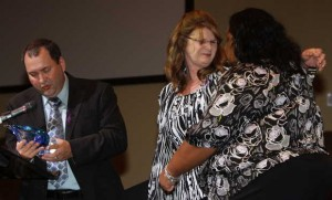Barbara Weatherford hugs Victims Assistance Coordinator Franchelle Daniels as Diamondhead Police Chief and former Gulfport Police Chief Alan Weatherford presents Daniels with a special award during the National Crime Victims' Rights Week ceremony in Gulfport on Thursday. The Weatherfords lost their daughter to a drunken driver in 2011. JOHN FITZHUGH — SUN HERALD